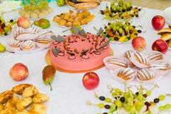 Εξυπηρετούμενοι πίνακες στο συμπόσιο Επιδόρπια, φρούτα και ζύμες στον μπουφέ catering στοκ φωτογραφία με δικαίωμα ελεύθερης χρήσης