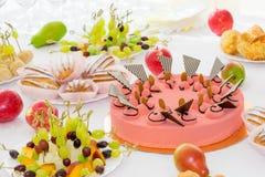 Εξυπηρετούμενοι πίνακες στο συμπόσιο Επιδόρπια, φρούτα και ζύμες στον μπουφέ catering στοκ εικόνες