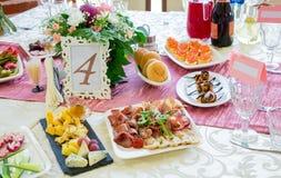 Εξυπηρετούμενοι πίνακες στο συμπόσιο Ποτά, πρόχειρα φαγητά, λιχουδιές και λουλούδια στο εστιατόριο Ένα γεγονός ή ένας γάμος gala στοκ εικόνες