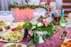 Εξυπηρετούμενοι πίνακες στο συμπόσιο Ποτά, πρόχειρα φαγητά, λιχουδιές και λουλούδια στο εστιατόριο Ένα γεγονός ή ένας γάμος gala στοκ εικόνα