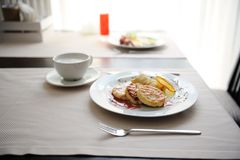 Εξυπηρετούμενο πρόγευμα στο εστιατόριο Τηγανίτες τυριών εξοχικών σπιτιών με τις πορτοκαλιούς μπούκλες και τον καφέ Στοκ Εικόνες