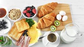Εξυπηρετώντας άσπρη ξύλινη τοπ άποψη τροφίμων προγευμάτων επιτραπέζιου πλήρης φρέσκια νόστιμη πρωινού υγιής απόθεμα βίντεο