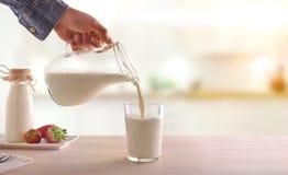 Εξυπηρετώντας γάλα προγευμάτων με μια κανάτα σε ένα γυαλί σε ένα άσπρο ξύλινο Κ στοκ εικόνα