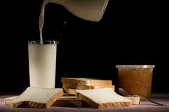 Εξυπηρετώντας γάλα με τις φέτες του ψωμιού και της μαρμελάδας στο μαύρο υπόβαθρο Στοκ εικόνα με δικαίωμα ελεύθερης χρήσης