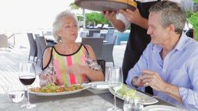 Εξυπηρετώντας πίτσα σερβιτόρων στο ανώτερο ζεύγος στο υπαίθριο εστιατόριο απόθεμα βίντεο