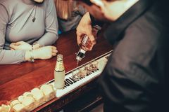 Εξυπηρετώντας πυροβολισμοί μπάρμαν του οινοπνευματώδους ποτού στο φραγμό νύχτας στοκ φωτογραφία