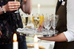 Εξυπηρετώντας σαμπάνια σερβιτόρων και χυμός από πορτοκάλι Στοκ Εικόνες