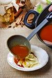 Εξυπηρετώντας σούπα ντοματών. Χύνοντας σούπα σε ένα πιάτο Στοκ Φωτογραφία