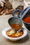 Εξυπηρετώντας σούπα ντοματών. Χύνοντας σούπα σε ένα πιάτο Στοκ Εικόνες