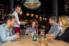Εξυπηρετώντας τρόφιμα σερβιτόρων στους πελάτες στον πίνακα στον καφέ Στοκ Φωτογραφίες