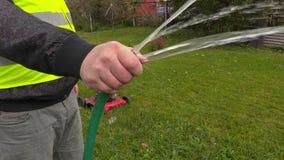 Εξωραΐζοντας εργαζόμενος με με τη μάνικα νερού φιλμ μικρού μήκους