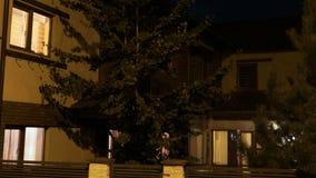 Εξωτερικό ενός κίτρινου ευρωπαϊκού έξυπνου σπιτιού από την κατοικημένη γειτονιά αυτόματα που φωτίζεται σε κάθε δωμάτιο -