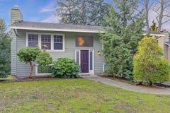 Εξωτερικό ενός ωραία ανακαινισμένου σπιτιού με πράσινο να πλαισιώσει και την άσπρη περιποίηση στοκ εικόνες