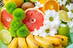 εξωτικοί καρποί τροπικοί γκρέιπφρουτ, μπανάνα, πορτοκάλι ακτινίδιων ασβέστη με τα λουλούδια Στοκ Εικόνες