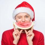 Εξωτικός εορτασμός Χριστουγέννων Εξωτικές χειμερινές διακοπές και διακοπές Το κορίτσι Χριστουγέννων τρώει το καρπούζι Λαβή καπέλω στοκ εικόνα με δικαίωμα ελεύθερης χρήσης
