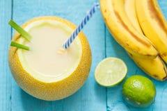 Εξωτικός πρόσφατα συμπιεσμένος χυμός με το κίτρινους πεπόνι και τον ασβέστη μπανανών στοκ εικόνα με δικαίωμα ελεύθερης χρήσης