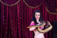 Εξωτικός χορευτής κοιλιών με το μεγάλο φίδι στη σκηνή στοκ εικόνα με δικαίωμα ελεύθερης χρήσης