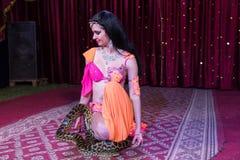 Εξωτικός χορευτής που γονατίζει στη σκηνή με το μεγάλο φίδι στοκ φωτογραφία