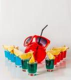 Εξωτικό ποτό σε ένα σφαίρα-διαμορφωμένο γυαλί, ένδεκα ποτά shotglas Στοκ Εικόνες