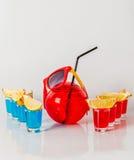 Εξωτικό ποτό σε ένα σφαίρα-διαμορφωμένο γυαλί, οκτώ ποτά shotglass Στοκ Εικόνα
