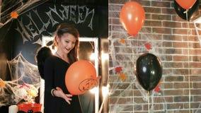 Εορτασμός αποκριών, νέο μπαλόνι παιχνιδιού μαγισσών με την κολοκύθα, κορίτσι εφήβων που φορά το τρομακτικό κοστούμι απόθεμα βίντεο