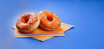 Εορτασμός της ημέρας βασιλιάδων ` s στις Κάτω Χώρες Διακοπές διασκέδασης Πορτοκαλιά γλυκά donats σε ένα μπλε υπόβαθρο Ελεύθερου χ Στοκ Φωτογραφίες