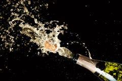 Εορτασμός του θέματος γενεθλίων, επετείου ή Χριστουγέννων Έκρηξη του ραντίσματος του λαμπιρίζοντας κρασιού σαμπάνιας με τον πετών Στοκ Φωτογραφία