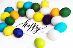 Εορταστικά ζωηρόχρωμα αυγά Πάσχας σε ένα άσπρο υπόβαθρο με μια καλλιγραφία ` ευτυχές Πάσχα ` ευχετήριων καρτών αυγά κίτρινα, μπλε Στοκ Εικόνα