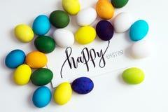 Εορταστικά ζωηρόχρωμα αυγά Πάσχας σε ένα άσπρο υπόβαθρο με μια καλλιγραφία ` ευτυχές Πάσχα ` ευχετήριων καρτών αυγά κίτρινα, μπλε Στοκ Εικόνες