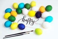 Εορταστικά ζωηρόχρωμα αυγά Πάσχας σε ένα άσπρο υπόβαθρο με μια καλλιγραφία ` ευτυχές Πάσχα ` ευχετήριων καρτών αυγά κίτρινα, μπλε Στοκ εικόνα με δικαίωμα ελεύθερης χρήσης