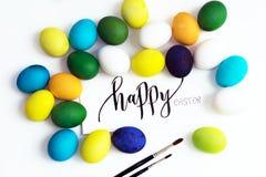 Εορταστικά ζωηρόχρωμα αυγά Πάσχας σε ένα άσπρο υπόβαθρο με μια καλλιγραφία ` ευτυχές Πάσχα ` ευχετήριων καρτών αυγά κίτρινα, μπλε Στοκ Φωτογραφία
