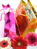 Εορταστικά ζωηρόχρωμα τσάντες δώρων και λουλούδια gerbera Στοκ Φωτογραφία
