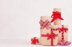 Εορταστικά κιβώτια δώρων του εγγράφου του Κραφτ με τις κόκκινες κορδέλλες στο λευκό ξύλινο πίνακα Πρότυπο για τη διαφήμιση και το στοκ φωτογραφία