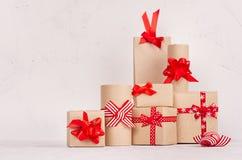 Εορταστικά κιβώτια δώρων του εγγράφου του Κραφτ με τις κόκκινες κορδέλλες στο λευκό ξύλινο πίνακα Πρότυπο για τη διαφήμιση και το στοκ φωτογραφίες με δικαίωμα ελεύθερης χρήσης