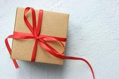 Εορταστικά κουτιά από χαρτόνι που τυλίγονται στην κόκκινη κορδέλλα στον πίνακα στοκ φωτογραφίες