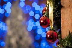 Εορταστικά δώρα, σφαίρες Χριστουγέννων και φω'τα γιρλαντών στο υπόβαθρο Εορταστική νέα διακόσμηση έτους Στοκ Εικόνες