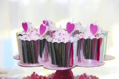 εορταστικά cupcakes σε μια λαμπρή συσκευασία με τη διακόσμηση υπό μορφή κρέμας και ρόδινων καρδιών στοκ εικόνες