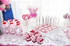 εορταστικές επιτραπέζιες διακοσμήσεις με τα cupcakes, τα γλυκά και τα δώρα στο ρόδινο χρώμα στοκ φωτογραφίες με δικαίωμα ελεύθερης χρήσης