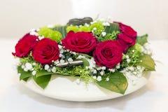 Εορταστικές floral ρυθμίσεις των κόκκινων τριαντάφυλλων Στοκ Φωτογραφία