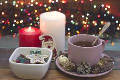 Εορταστική ακόμα ζωή με ένα φλυτζάνι του τσαγιού, κύπελλο των καραμελών και των καίγοντας κεριών Στοκ Φωτογραφίες