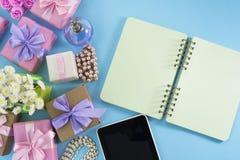 Εορταστική ανθοδέσμη τόξων κορδελλών σατέν δώρων κιβωτίων αφισών υποβάθρου του μπλε υποβάθρου smartphone ταμπλετών σημειωματάριων Στοκ Φωτογραφία
