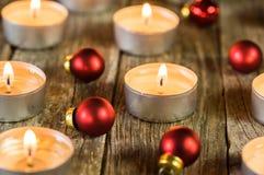 Εορταστική διάθεση Χριστουγέννων με τα κεριά και τις κόκκινες διακοσμήσεις μπιχλιμπιδιών στοκ εικόνες