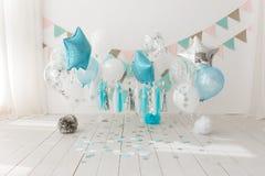 Εορταστική διακόσμηση υποβάθρου για τον εορτασμό γενεθλίων με το γαστρονομικό κέικ και τα μπλε μπαλόνια στο στούντιο, συντριβή κέ στοκ φωτογραφία