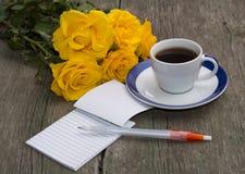 Εορταστική κάρτα, κίτρινα τριαντάφυλλα, σημειωματάριο και καφές Στοκ Φωτογραφίες