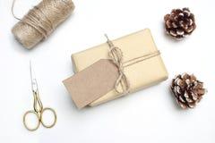 Εορταστική ορισμένη σύνθεση εικόνας αποθεμάτων Χριστουγέννων Χειροποίητο κιβώτιο δώρων με την ετικέττα δώρων εγγράφου τεχνών, pin Στοκ Φωτογραφίες