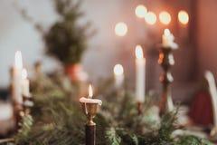 Εορταστική ρύθμιση επιτραπέζιων διακοσμήσεων Χριστουγέννων με το κάψιμο των κεριών και των κλάδων έλατου Στοκ Εικόνες