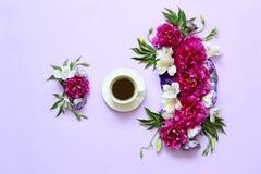 Εορταστική ρύθμιση λουλουδιών των peonies σε ένα ρόδινος-πορφυρό υπόβαθρο και ένα φλιτζάνι του καφέ Στοκ φωτογραφίες με δικαίωμα ελεύθερης χρήσης