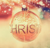 Εορταστική σφαίρα διακοσμήσεων γυαλιού Χριστουγέννων με τα Χριστούγεννα κειμένων στο θολωμένο δωμάτιο και bokeh το φωτισμό Στοκ φωτογραφία με δικαίωμα ελεύθερης χρήσης