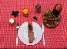 Εορταστική σύνθεση με τα κεριά και τα πιάτα πίνακας πιάτων πετσετών διακοσμήσεων Ένας όμορφος πίνακας που θέτει, κόκκινο επιτραπέ Στοκ Φωτογραφίες
