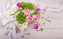 Εορταστική σύνθεση λουλουδιών στο άσπρο ξύλινο υπόβαθρο Υπερυψωμένη όψη Στοκ φωτογραφίες με δικαίωμα ελεύθερης χρήσης